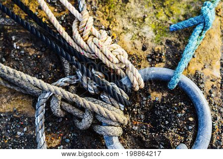 Ropes attached to metal ring in a harbour, grungy texture
