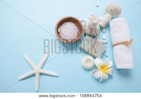 salt in bowl , frangipani ,candle,soap with herbal ball ,starfish on blue background