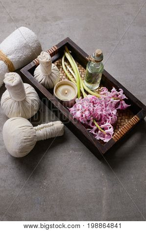 Spa setting pink Hyacinth with and ball, salt in bowl,oil, candle in basket ,towelon gray background