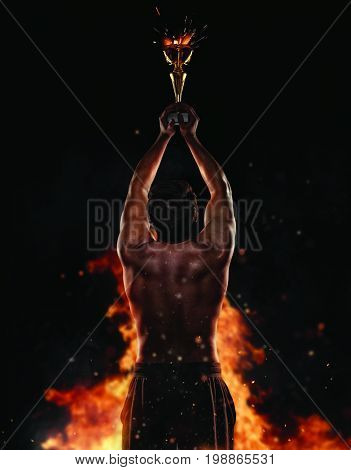 Back view of man fighter holding trophy cup in hands, victory gesture, fire on background. Concept of hard work, glory and success. Very high resolution image