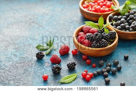 Various summer fruits in a wooden bowls. Assorted fresh berries with leaves on metal background.