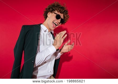 Happy excited young man in white shirt and jacket celebrating success and clapping hands isolated over red background