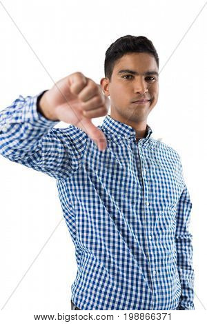 Portrait of displeased man showing thumb sign against white background