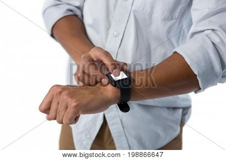 Mid section of man using smartwatch against white background