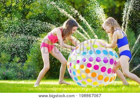 Two Adorable Little Girls Playing With Inflatable Beach Ball In A Backyard On Sunny Summer Day. Cute
