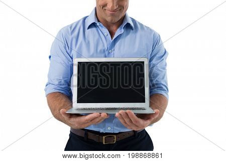 Male executive holding laptop against white background