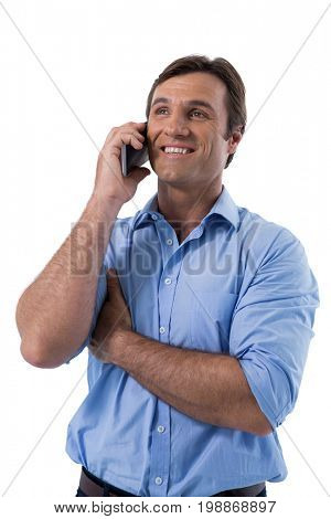 Male executive talking on mobile phone against white background