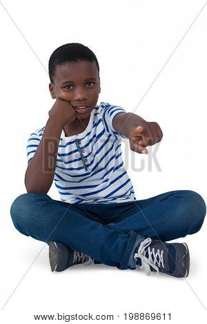 Portrait of sad boy pointing his finger against white background