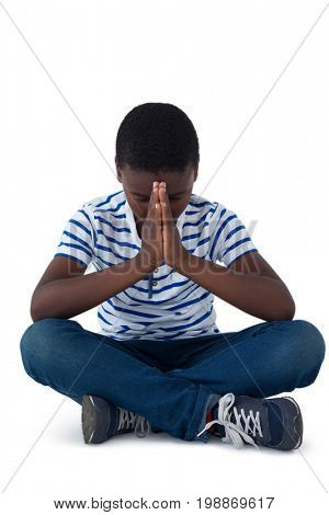 Boy sitting on floor and praying against white background