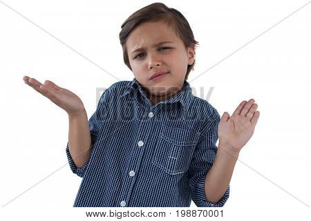 Frowning boy shrugging his shoulders against white background