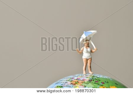 a miniature old woman wearing swimsuit and holding an umbrella above her head on the top of the terrestrial globe, and a negative space on the left