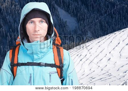 Portrait of young man mountaineer in the winter mountains. White snowy mountain slope and forest.