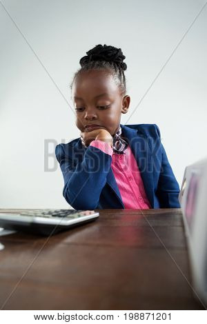 Serious businesswoman with hand on chin looking at calculator while sitting in office