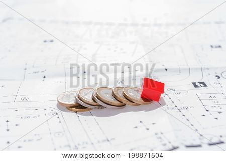 Real estate investment, Red house with coins on ground plan