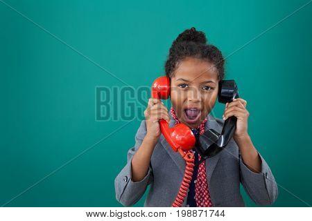 Portrait of surprised businesswoman talking land line phones against blue background