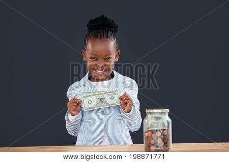 Portrait of cheerful businesswoman with coins jar showing paper currency at desk against glass jar in office