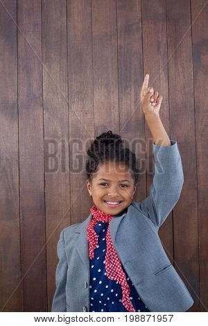 Portrait of smiling girl pretending as businesswoman standing with arms raised against wooden wall