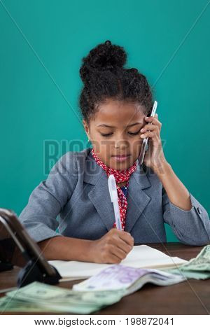 Close up of businesswoman using phone while writing on book by paper currency at desk against blue background