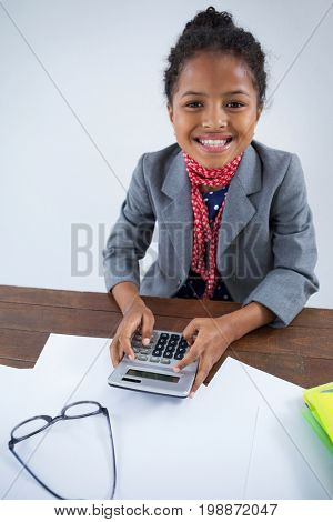 Portrait of smiling girl pretending as businesswoman using calculator while working at desk