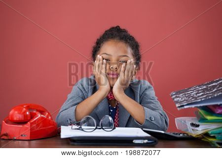 Portrait of bored businesswoman with hand on chin sitting at desk against orange background
