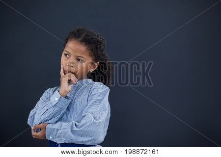 Thoughtful girl with hand on chin looking away while standing against black background