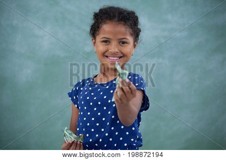Portrait of girl giving paper currency while standing against wall