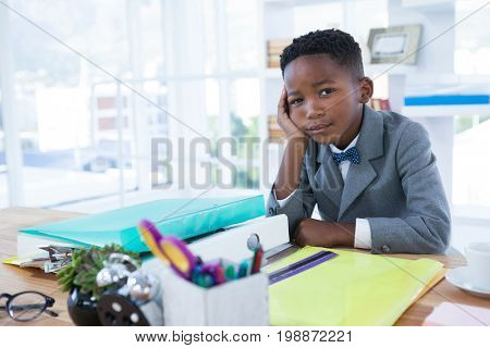 Portrait of businessman with hand on chin sitting at desk in office