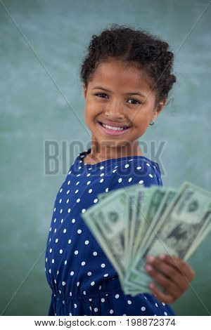 Portrait of girl showing paper currency while standing against wall