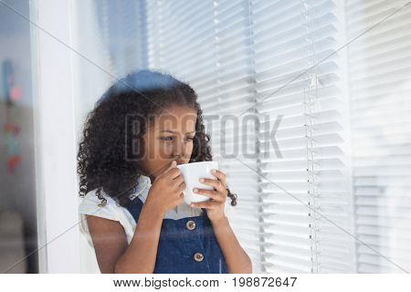 Girl imitating as businesswoman having coffee while standing by window seen through glass