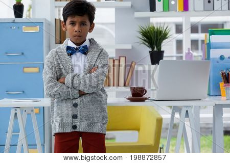 Portrait of boy pretending as businessman standing with arms crossed by desk in office