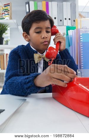 Boy pretending as businessman talking on land line phone at desk in office