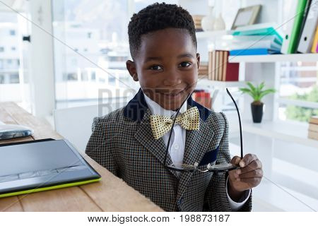 Portrait of smiling boy imitating as businessman holding eyeglasses while sitting at desk in office