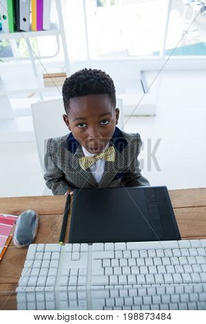 High angle view of boy imitating as businessman sitting at desk in office