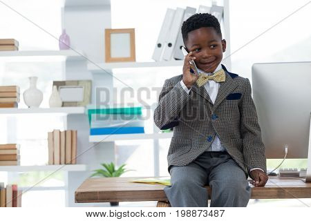 Boy imitating as businessman talking on smart phone while sitting on desk in office