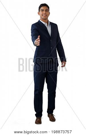 Portrait of smiling businessman extending arms for handshake while standing against white background