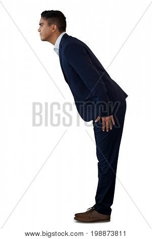 Side view of businessman bowing while standing against white background