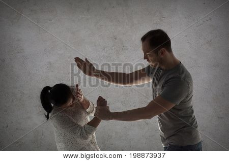 domestic violence, people and abuse concept - couple having fight and man beating woman over gray concrete background