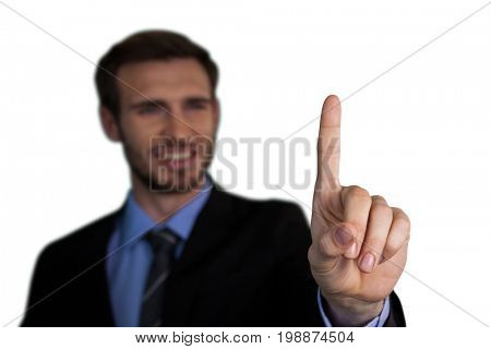 Close up of smiling businessman touching index finger on invisible interface against white background