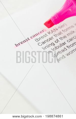 Cropped image of pink felt tip pen with Breast Cancer text on paper against white background