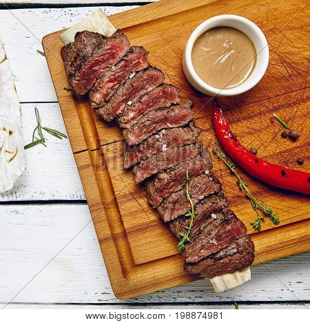 Gourmet Grill Restaurant Beef Steak Menu - Skirt Steak on Wooden Plate. Black Angus Beef Steak. Beef Steak Dinner. Top View