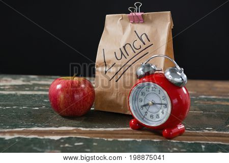 Close-up of apple, alarm clock and lunch bag on wooden table