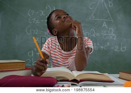 Thoughtful schoolgirl doing his homework in classroom