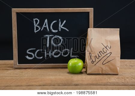 Lunch paper bag, green apple and slate with text back to school on wooden table against black background