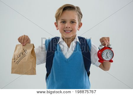 Portrait of smiling schoolboy holding alarm clock and lunch paper bag