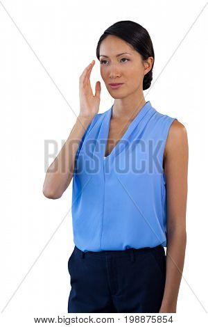 Thoughtful businesswoman looking away while gesturing against white background