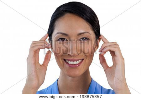 Close up portrait of smiling businesswoman adjusting invisible eyeglasses against white background