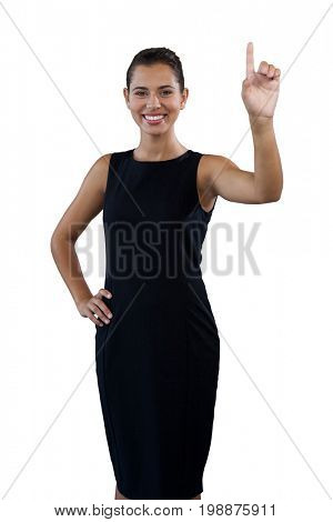 Portrait of happy young businesswoman touching invisible interface against white background