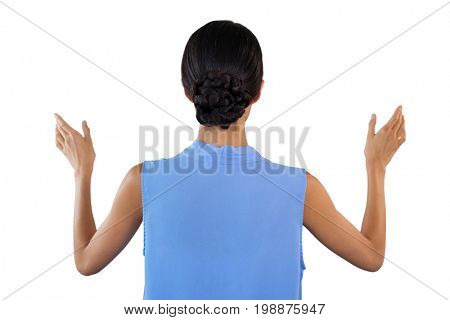 Rear view of businesswoman gesturing while using invisible interface against white bacground