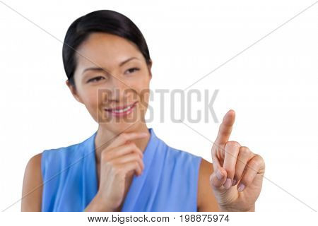 Smiling businesswoman with hand on chin touching interface against white background