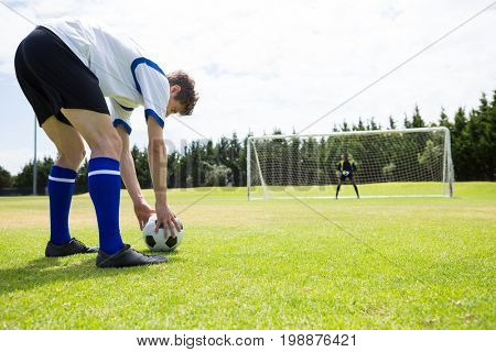 Young male soccer players playing against sky during sunny day